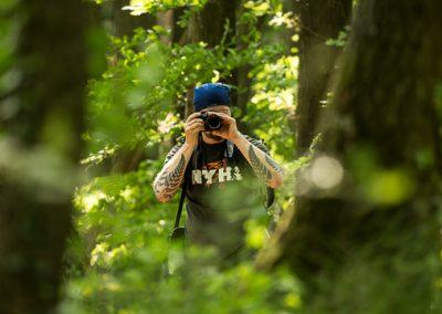 fotograf vordergrund zwischen baeumen